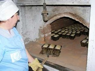 Посадка форм с тестом в печь, сельская пекарня.